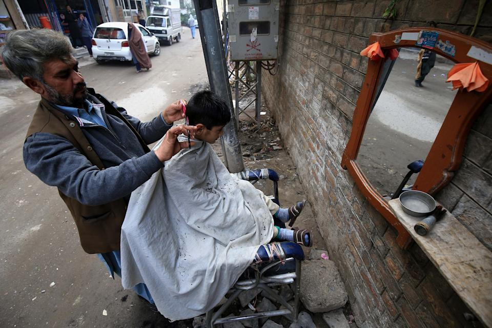 A barber gives a haircut to a customer at a roadside shop during World AIDS Day in Peshawar, Pakistan, 01 December 2020. According to doctors, cuts from razor blades that haven't undergone proper sterilization are among some of the main causes of AIDS spread. World AIDS Day, observed annually on 01 December, is dedicated to raising awareness against the spread of AIDS and HIV infections.  (EPA/ARSHAD ARBAB)EPA