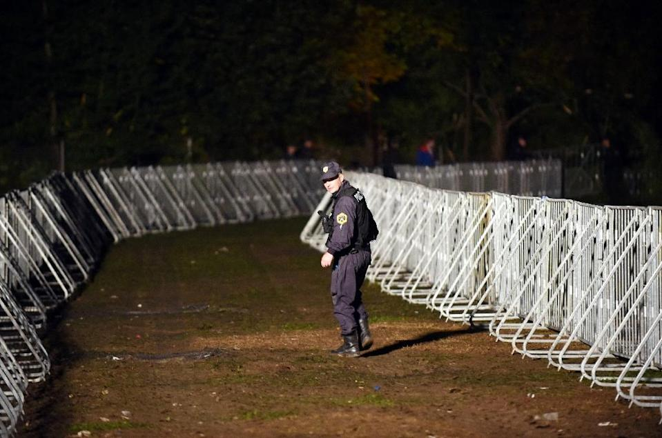 A Slovenian police officer walks through a reception camp for migrants and refugees in Brezice, Slovenia on October 21, 2015 (AFP Photo/)