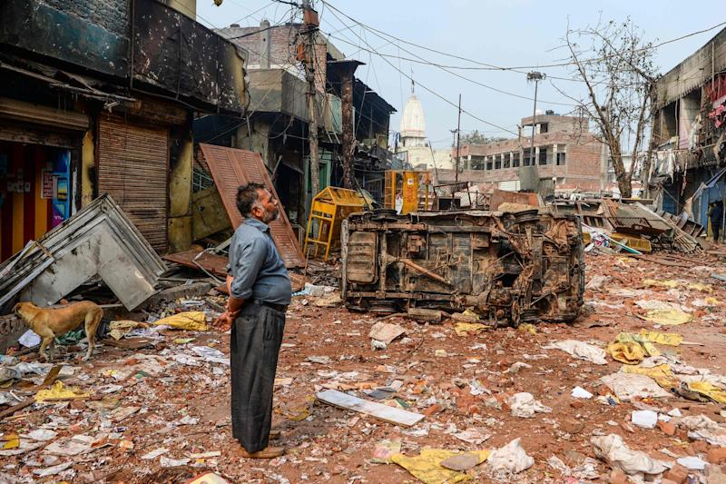 A resident stands by burned-out and damaged homes and shops following clashes in Delhi on Wednesday: AFP/Getty