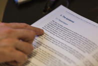 """FILE - In this Dec. 18, 2020 file photo, Francesco Zambon, lead author of a withdrawn World Health Organization (WHO) report into Italy's coronavirus response, shows his report during an interview with The Associated Press in Rome. Italian prosecutors formally accused top WHO official Ranieri Guerra of lying to them about a spiked U.N. report into Italy's coronavirus response, revealing private communications Friday that are likely to embarrass the U.N. agency. Emails show that Guerra tried to have one of the main report authors, Dr. Francesco Zambon, alter the data in the report to say that Italy had """"updated"""" its pandemic plan when it had not. (AP Photo/Domenico Stinellis, file)"""