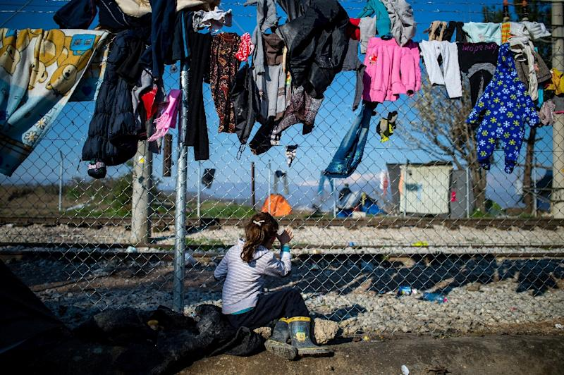 A migrant girl looks through a fence at a makeshift camp at the Greek-Macedonian border, near the village of Idomeni on March 19, 2016 (AFP Photo/Andrej Isakovic)