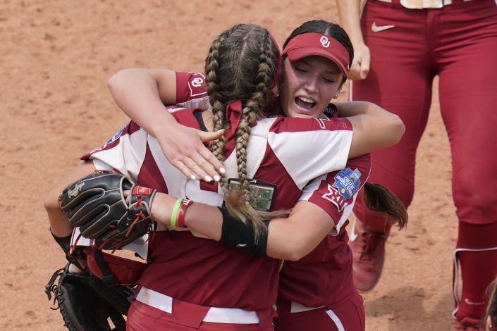 Oklahoma pitcher Nicole May, right, celebrates with catcher Kinzie Hansen, left, after Oklahoma defeated James Madison in an NCAA Women's College World Series softball game Sunday, June 6, 2021, in Oklahoma City. (AP Photo/Sue Ogrocki)