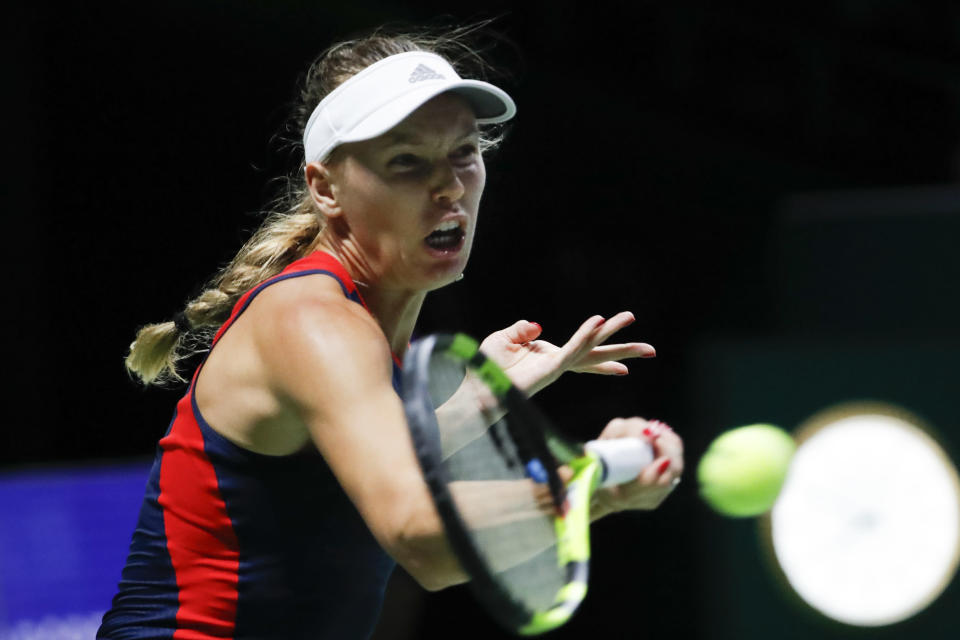 Caroline Wozniacki of Denmark plays a return shot while competing against Elina Svitolina of the Ukraine during their women's singles match at the WTA tennis finals in Singapore, Thursday, Oct. 25, 2018. (AP Photo/Vincent Thian)