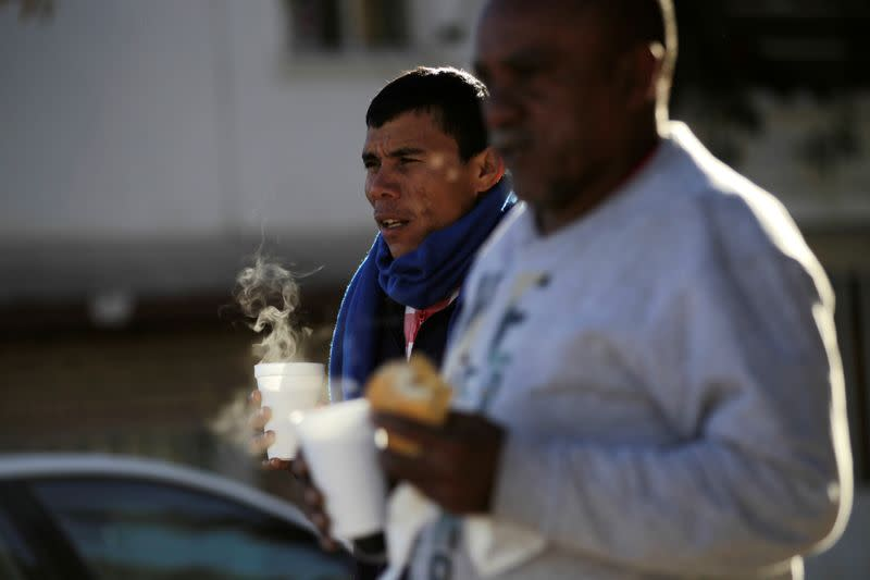 Migrants take caffee outside the Posada Belen migrant shelter, which is closed due to an outbreak of the coronavirus disease COVID-19, in Saltillo