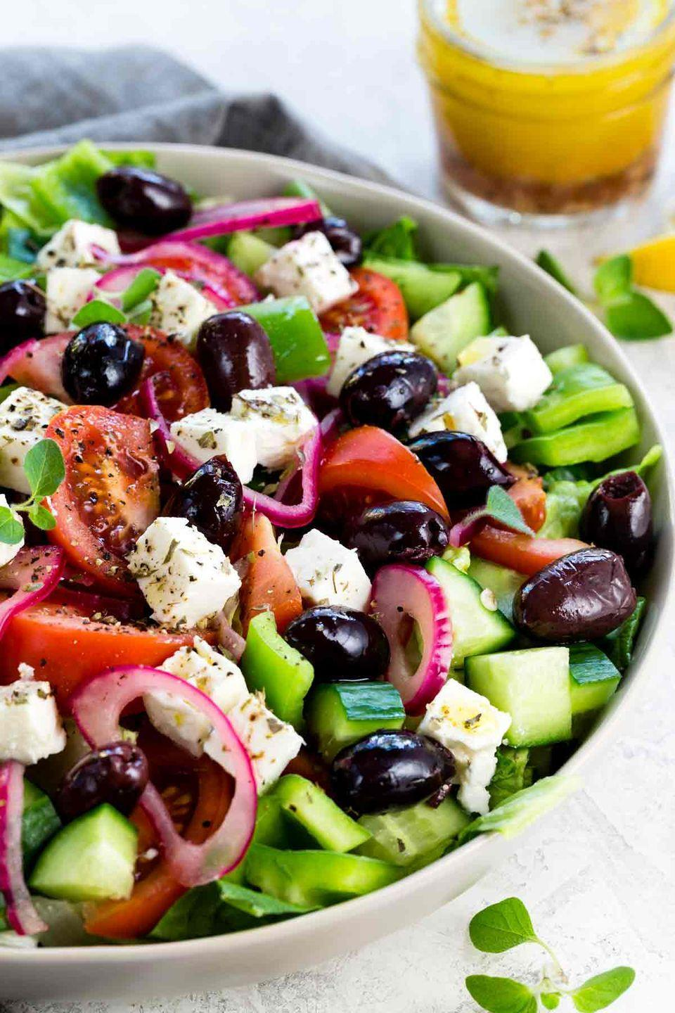 """<p>For a side that stands up to scorching heat better than mayo-based salads, try a super fresh mixture of romaine and Greek favorites, like cucumbers, kalamata olives, tomatoes, red onions, and feta. </p><p><a href=""""https://www.jessicagavin.com/greek-salad/"""" rel=""""nofollow noopener"""" target=""""_blank"""" data-ylk=""""slk:Get the recipe."""" class=""""link rapid-noclick-resp"""">Get the recipe.</a></p>"""