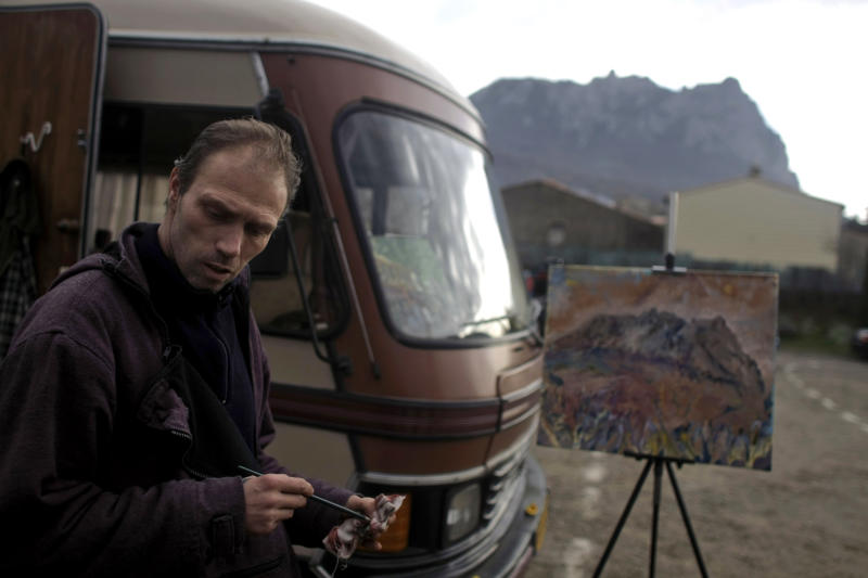 Stefano Ariu, a Dutch artist, puts the finishing touches to his painting depicting the Pic de Bugarach mountain in the town of Bugarach, France, Thursday, Dec. 20, 2012. The clock is ticking down to Dec. 21, the supposed end of the Mayan calendar, and from China to California to Mexico, thousands are getting ready for what they think is going to be a fateful day. The sleepy town of Bugarach, nestled in the French Pyrenees mountains, is bracing for the arrival of hundreds of New Age enthusiasts and UFO believers that want to witness the end of the Mayan Long Count calendar. (AP Photo/Marko Drobnjakovic)