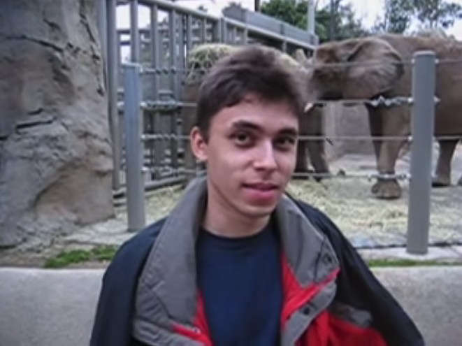A screenshot from the video ofJawed Karim posing in front of the elephant enclosure