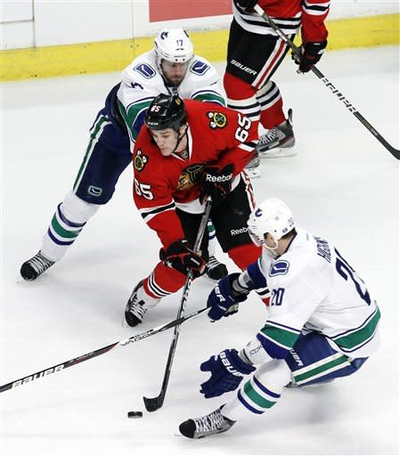 Chicago Blackhawks center Andrew Shaw (65) handles the puck between Vancouver Canucks center Ryan Kesler (17) and Chris Higgins (20) during the second period of an NHL hockey game in Chicago, Wednesday, March 21, 2012. (AP Photo/Charles Rex Arbogast)