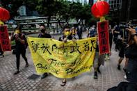 Raphael Wong holds a banner during the protest near the official ceremony