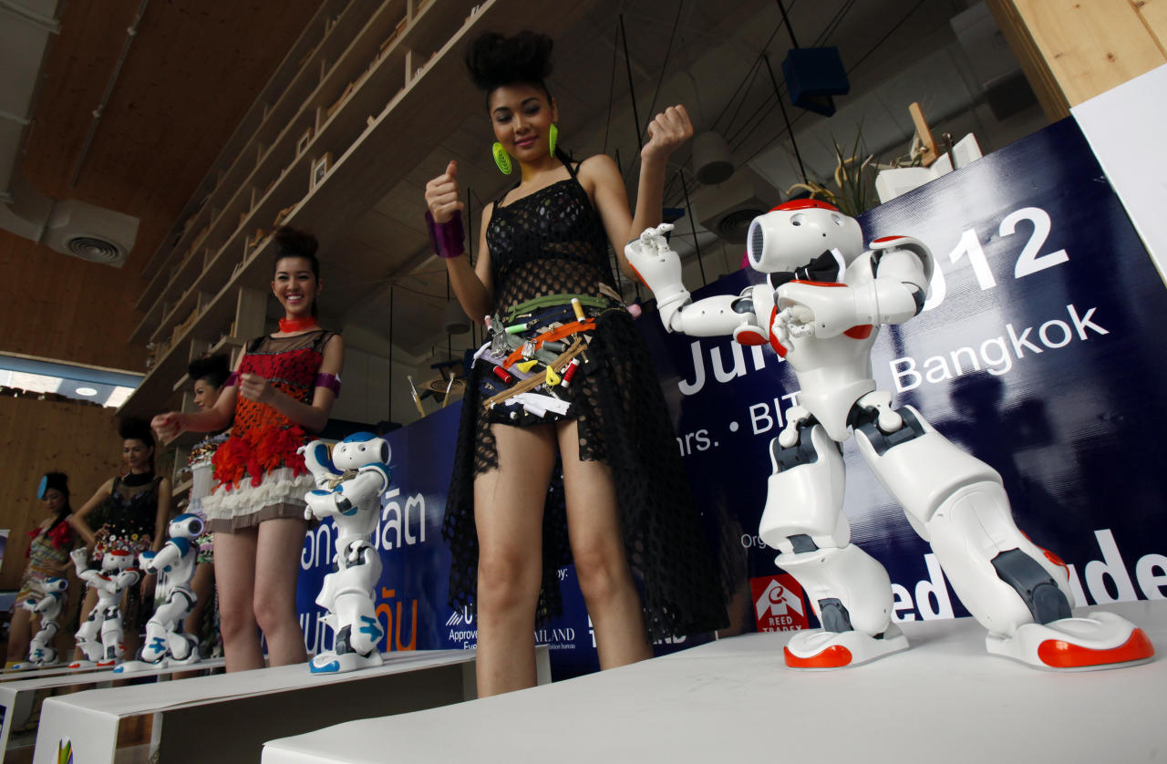 "Models dance with the humanoid robot ""NAO"" during a news conference in Bangkok June 19, 2012. NAO, the newest humanoid technology from Europe, was brought in to promote ""Thailand's Manufacturing Expo 2012"" which will be held from June 21-24 in Bangkok. REUTERS/Chaiwat Subprasom (THAILAND - Tags: SCIENCE TECHNOLOGY BUSINESS)"