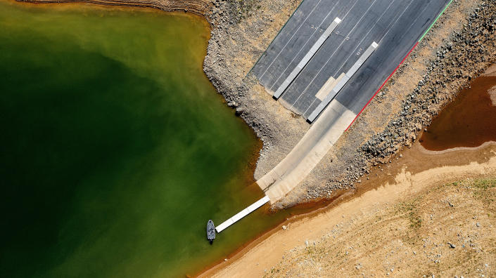 A launch ramp, extended to accommodate low water levels, stretches into Lake Oroville on Saturday, May 22, 2021, in Oroville, Calif. At the time of this photo, the reservoir was at 39 percent of capacity and 46 percent of its historical average. California officials say the drought gripping the U.S. West is so severe it could cause one of the state's most important reservoirs to reach historic lows by late August, closing most boat ramps and shutting down a hydroelectric power plant during the peak demand of the hottest part of the summer. (AP Photo/Noah Berger)