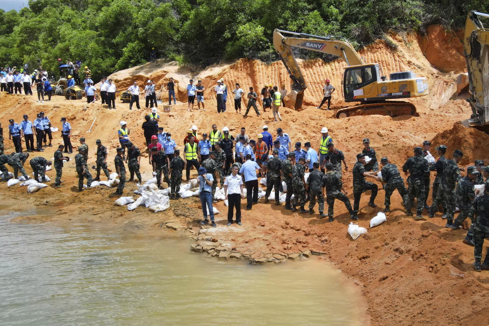 Rescuers work to build an embankment at the site of a flooded tunnel in Zhuhai in southern China's Guangdong Province, Thursday, July 15, 2021. Rescuers were pumping out water Thursday to try to find 14 construction workers trapped by a flood in a tunnel being built in southern China. The rescuers have not been able to contact the workers missing since the 3:30 a.m. flood, the Zhuhai city emergency management department said in an online post. (Chinatopix via AP)
