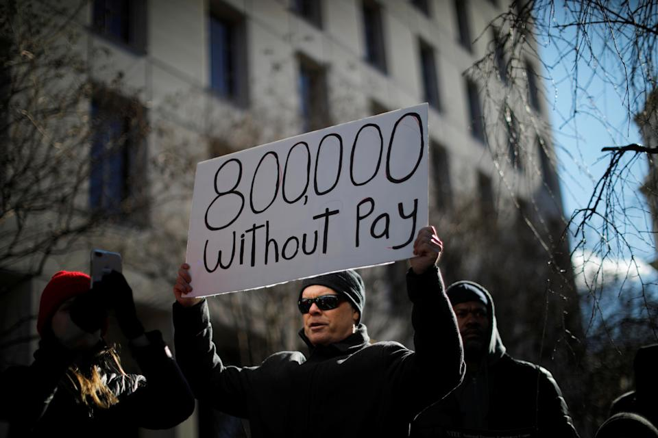 """A demonstrator holds a sign, signifying hundreds of thousands of federal employees who won't be receiving their paychecks as a result of the partial government shutdown, during a """"Rally to End the Shutdown"""" in Washington, D.C., Jan. 10, 2019. (Photo: Carlos Barria/Reuters)"""