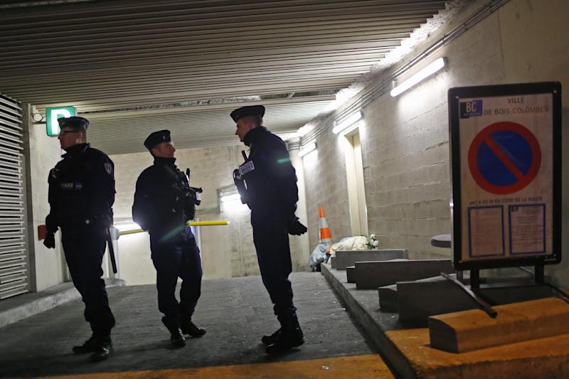 """Police officers stand guard in front of the entrance of a parking lot where a man, believed to be the suspect in a Paris newspaper office shooting, was detained, in Bois Colombes, outside Paris, Thursday, Nov. 21, 2013. Agnes Thibault-Lecuivre, a spokeswoman for the French prosecutor's office, said that """"a suspect with a strong resemblance to the shooter"""" was arrested in an underground parking lot in Bois-Colombes, 10 kilometers (6 miles) north of Paris. (AP Photo/Thibault Camus)"""