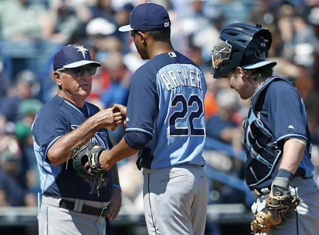 Tampa Bay Rays manager Joe Maddon, left, congratulates Rays starting pitcher Chris Archer (22) during a fourth-inning pitching change during a spring training baseball game against the New York Yankees in Tampa, Fla., Sunday, March 9, 2014. Rays catcher Ryan Hanigan joins the pair on the mound for the change. (AP Photo/Kathy Willens)