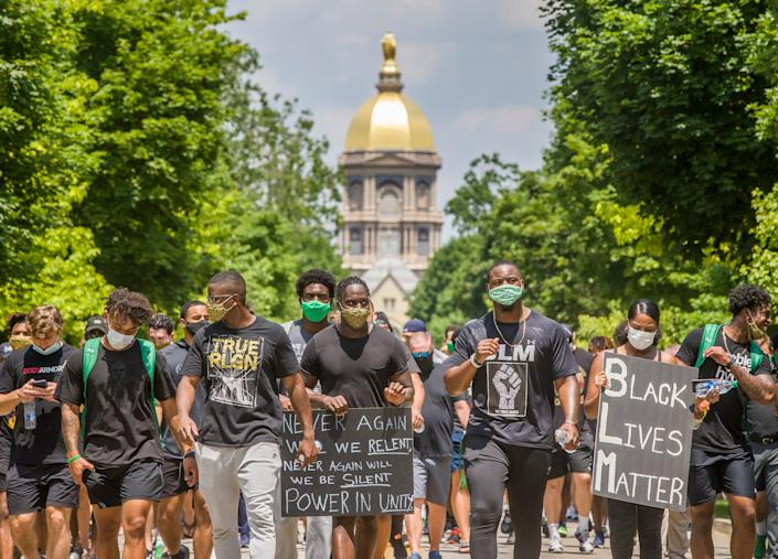 Notre Dame football players march with signs during a celebration of Juneteenth on Friday, June 19, 2020, at Notre Dame in South Bend, Ind.