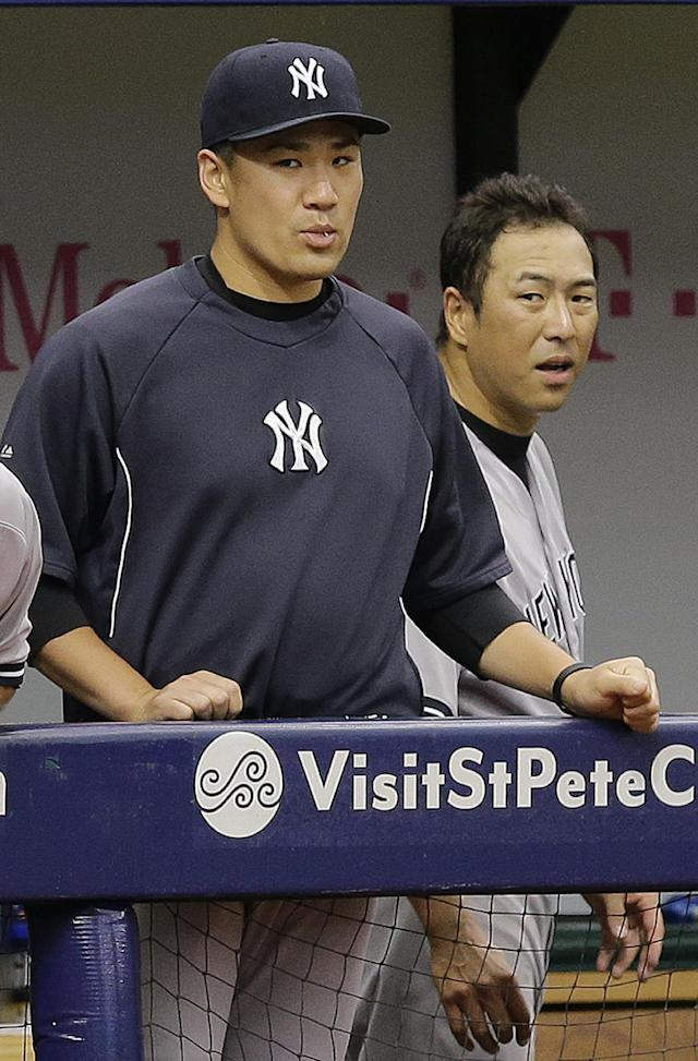 New York Yankees Masahiro Tanaka, left, of Japan, and Hiroki Kuroda, also of Japan, watch action against the Tampa Bay Rays during the fifth inning of a baseball game Sunday, Aug. 17, 2014, in St. Petersburg, Fla. (AP Photo/Chris O'Meara)
