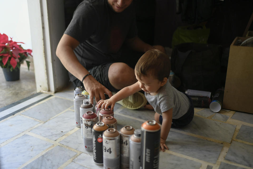 "Street artist Wolfgang Salazar takes inventory of his aerosol paints accompanied by his son Noah, in their home in the Petare neighborhood of Caracas, Venezuela, Monday, Dec. 28, 2020. Salazar has gained increasing fame for his spray-painted murals of Venezuelans — heroes and everyday folk alike. ""The main goal is that people see a reflection of themselves,"" said Salazar, who added that he hopes people will see the murals and say: ""I exist. What happens to me exists. I'm real. I feel identified."" (AP Photo/Matias Delacroix)"
