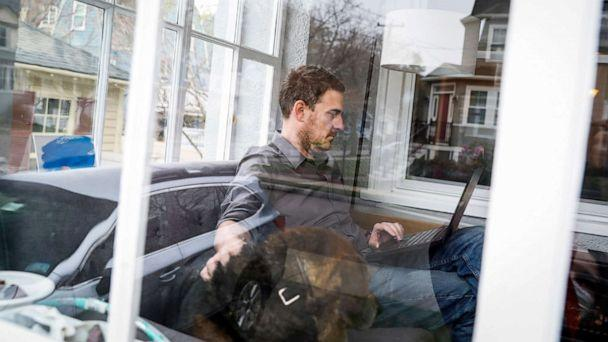 PHOTO: Ben Bradley, a product manager for a software company, while petting his family's dog, Tenley at their home in Melrose, Mass., April 24, 2020. (Boston Globe via Getty Images, FILE)