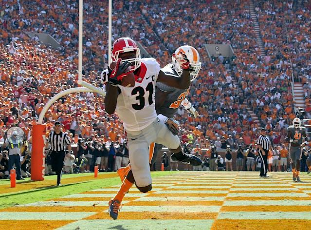 Georgia's Chris Conley (31) makes a touchdown catch in front of Tennessee's Justin Coleman (27) in the first half of an NCAA college football game in Knoxville, Tenn., Oct. 5, 2013. (AP Photo/Atlanta Journal-Constitution, Jason Getz)