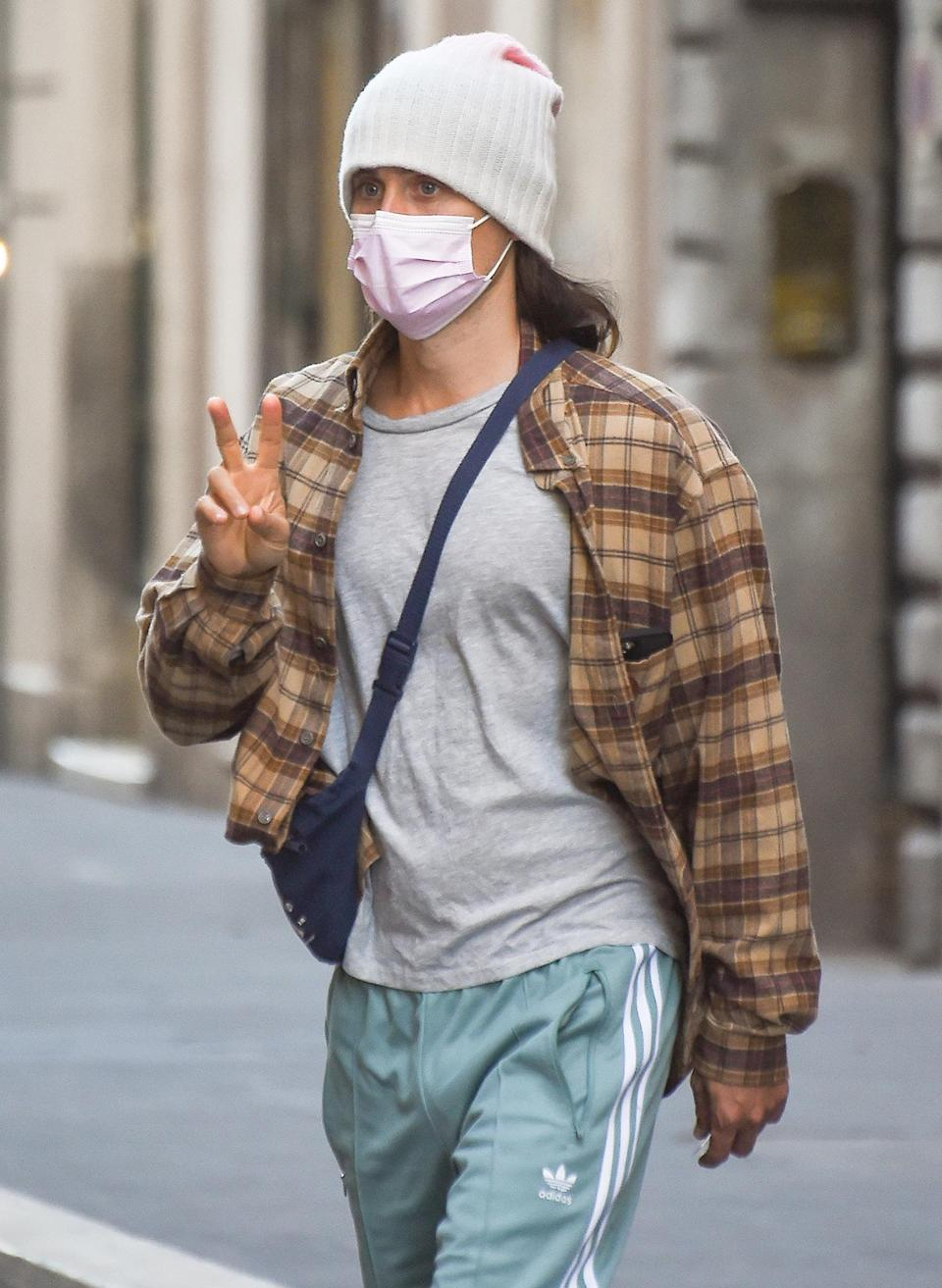 <p>Jared Leto shares a peace sign as he walks through Via del Corso on Sunday in Rome.</p>