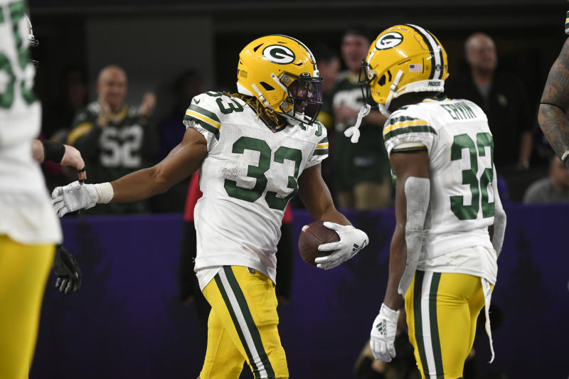 Green Bay Packers running back Aaron Jones (33) celebrates with Tyler Ervin after scoring on a 56-yard run during the second half of the team's NFL football game against the Minnesota Vikings, Monday, Dec. 23, 2019, in Minneapolis. (AP Photo/Craig Lassig)