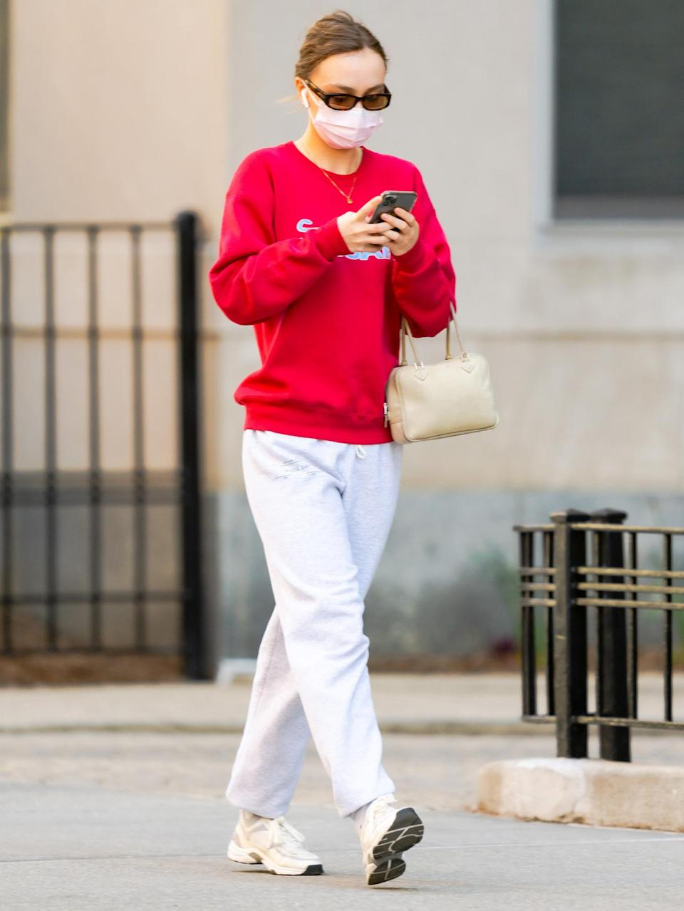 <p>Lily-Rose Depp checks her phone while out on a walk through N.Y.C. on Monday.</p>