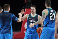 Slovenia's Luka Doncic celebrates with teammates at the end of a men's basketball preliminary round game against Spain at the 2020 Summer Olympics, Sunday, Aug. 1, 2021, in Saitama, Japan. (AP Photo/Charlie Neibergall)