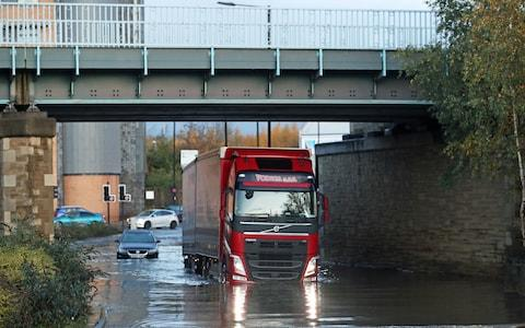 A lorry drives through floodwater near Meadowhall shopping centre in Sheffield - Credit: PA