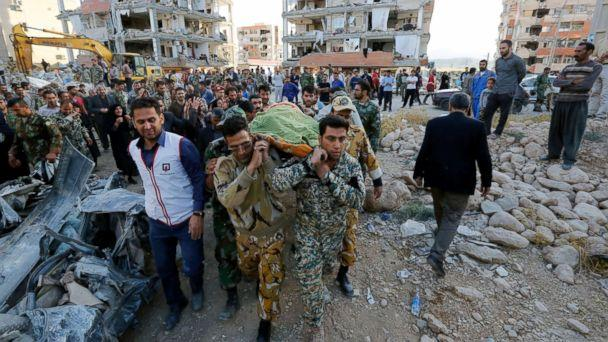 PHOTO: Iranian soldiers carry the body of an earthquake victim near the wreckage of a collapsed building in the city of Pole-Zahab, in Kermanshah Province, Iran, Nov. 13, 2017. (Abedin Taherkenareh/EPA)