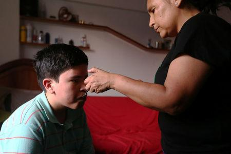 Ana Alvarez gives her son Anthony a spoonful of marijuana oil to soothe the symptoms of tuberous sclerosis and Lennox-Gastaut syndrome at her house in Lima, Peru, February 23, 2017. Picture taken February 23, 2017. REUTERS/Guadalupe Pardo