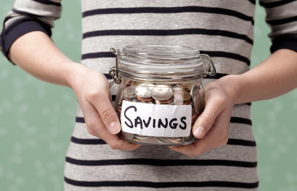 Woman holding a jar with a SAVINGS label on it. There are coins in the jar.
