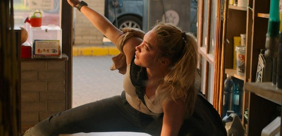 A woman crouching on the ground with her one foot stretched outward