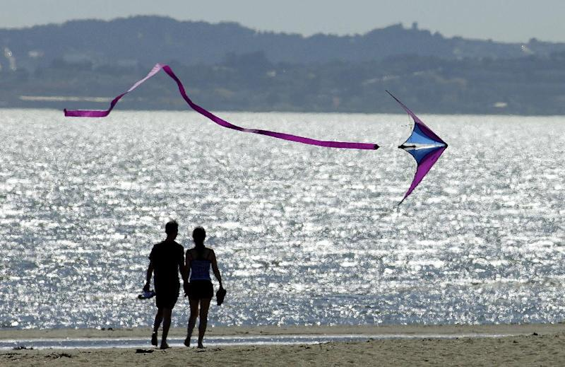A kite flys past a couple on Crown Memorial Beach Monday, May 12, 2014, in Alameda, Calif. After a hot, windy Mother's Day with temperatures in the mid-80s, a high pressure system was expected to heighten the heat slightly Monday before pushing it to near triple digits in some spots midweek, mostly inland areas already badly parched by drought. High temperatures will extend up and down California, according to the National Weather Service. (AP Photo/Ben Margot)