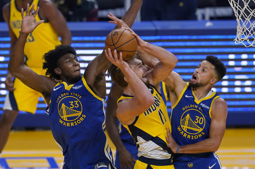 Indiana Pacers forward Domantas Sabonis, middle, shoots between Golden State Warriors center James Wiseman (33) and guard Stephen Curry (30) during the first half of an NBA basketball game in San Francisco, Tuesday, Jan. 12, 2021. (AP Photo/Jeff Chiu)