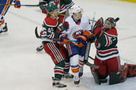 New York Islanders center Jean-Gabriel Pageau (44) gets sandwiched between New Jersey Devils defenseman Sami Vatanen (45) and New Jersey Devils goaltender Aaron Dell (47) during the first period of an NHL hockey game, Tuesday, March 2, 2021, in Newark, N.J. (AP Photo/Kathy Willens)