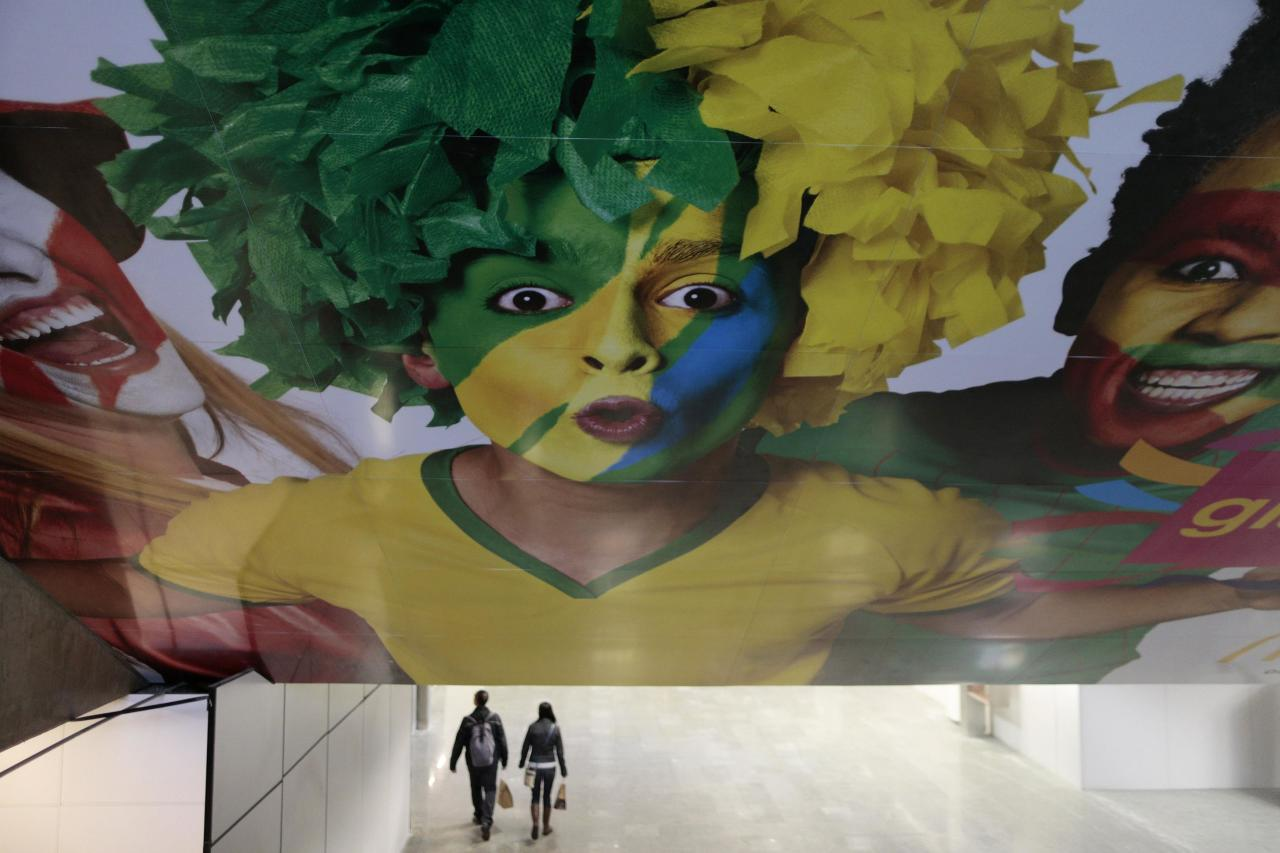 Passengers walk near advertising panels depicting the World Cup in Brasilia International airport in Brasilia, June 2, 2014. Brasilia is one of the host cities for the World Cup in Brazil. REUTERS/Ueslei Marcelino (BRAZIL - Tags: SPORT SOCCER WORLD CUP SOCIETY)