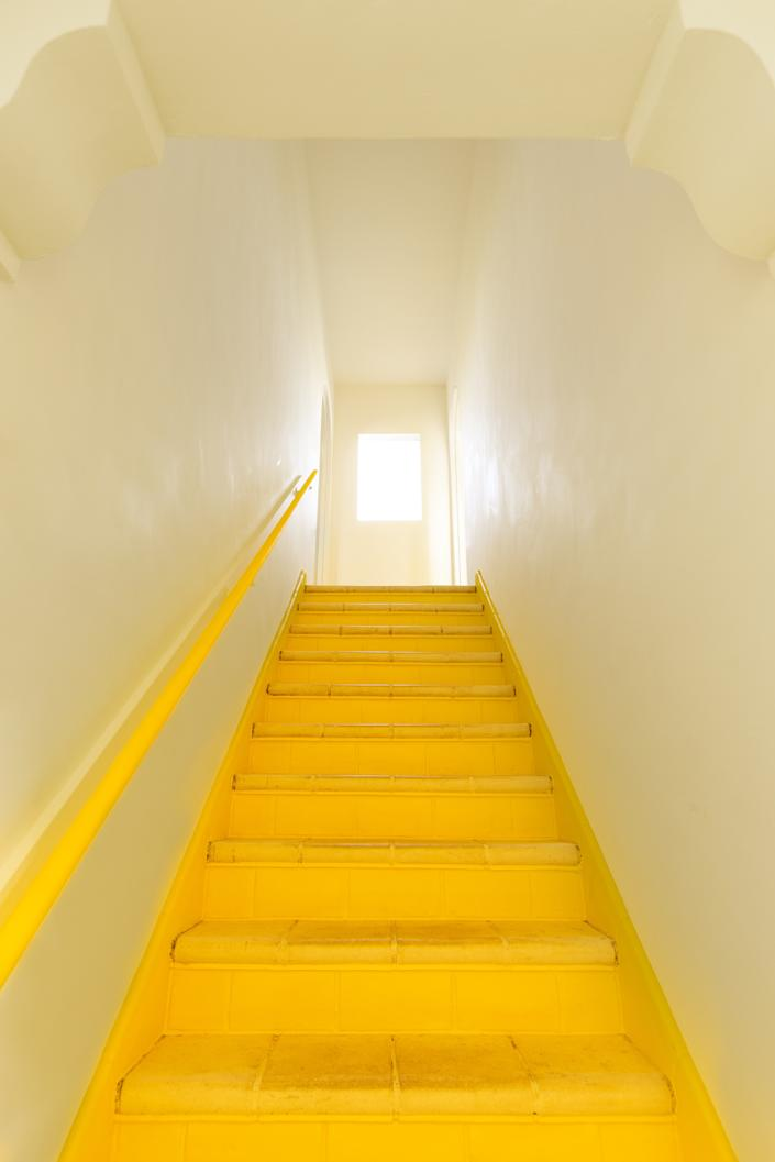 """The designer chose Benjamin Moore Bold Yellow for the home's interior stairwell. """"When the color reflects off the white walls, it makes the whole space glow,"""" she says."""