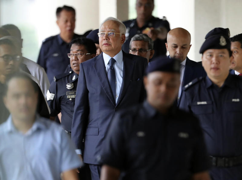FILE - In this Oct. 4, 2018, file photo, former Malaysian Prime Minister Najib Razak, center, walks out of courtroom at Kuala Lumpur High Court in Kuala Lumpur, Malaysia. Najib is hardly lying low ahead of his corruption trial set to begin Tuesday, Feb. 12, 2019, on charges related to the multibillion-dollar looting of the 1MDB state investment fund. He's crooned about slander in an R&B video and vilified the current government on social media to counter portrayals of him as corrupt and out of touch. Najib denies wrongdoing and his lawyers are seeking delay.(AP Photo/Vincent Thian, File)