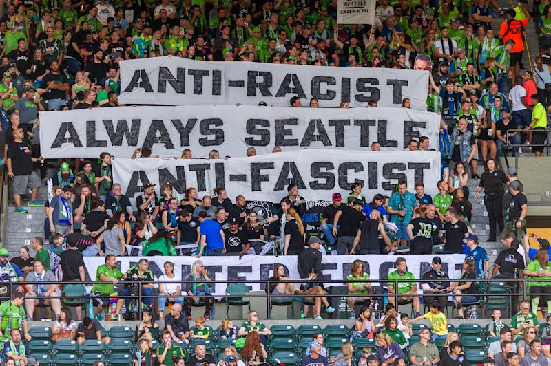 PORTLAND, OR - AUGUST 23: Seattle Sounders supporters group ECS (Emerald City Supporters) remained silent for the first 33 minutes of the game to denounce MLS stand on the iron front symbol during the Seattle Sounders 2-1 victory over the Portland Timbers at Providence Park on August 23, 2019 in Portland, OR (Photo by Diego Diaz/Icon Sportswire via Getty Images).