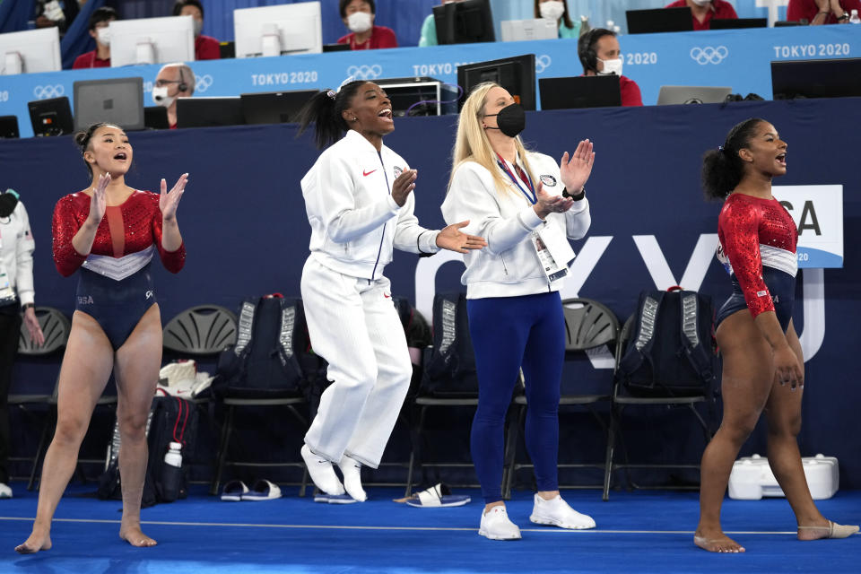 FILE - In this July 27m 2021 file photos, gymnasts from the United States, Simone Biles, center, Jordan Chiles , right, and Sunisa Lee cheer Grace McCallum as she performs on the floor during the artistic gymnastics women's final at the 2020 Summer Olympics, in Tokyo. Biles and Naomi Osaka are prominent young Black women under the pressure of a global Olympic spotlight that few human beings ever face. But being a young Black woman -- which, in American life, comes with its own built-in pressure to perform -- entails much more than meets the eye. (AP Photo/Ashley Landis, File)