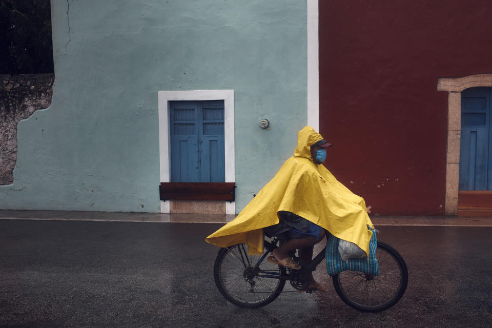 A man cycles along an empty street after the passing of Hurricane Delta in Valladolid, Mexico, Wednesday, Oct. 7, 2020. Hurricane Delta made landfall Wednesday just south of the Mexican resort of Cancun as a Category 2 storm, downing trees and knocking out power along the northeastern coast of the Yucatan Peninsula. (AP Photo/Andres Kudacki)