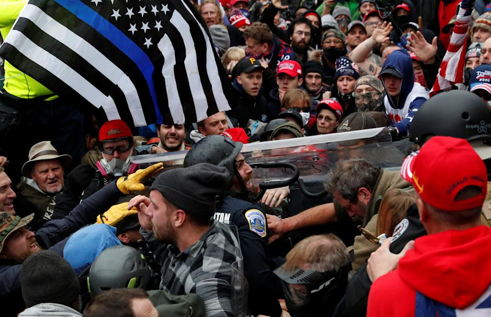 A police officer is dragged in a crowd of pro-Trump protesters during a clash at a rally to contest the certification of the 2020 US presidential election results. Photo: Shannon Stapleton/Reuters