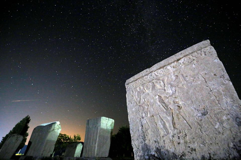 A meteor streaks past stars in the night sky above medieval tombstones during the Perseid meteor shower in Radimlja near Stolac, Bosnia and Herzegovina (Reuters)