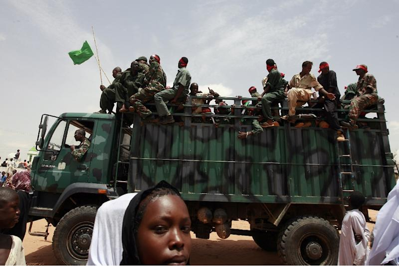 A Sudanese girl walks past a truck carrying leaving soldiers following a visit by President Omar al-Bashir in the West Darfur state capital of El Geneina on July 24, 2008