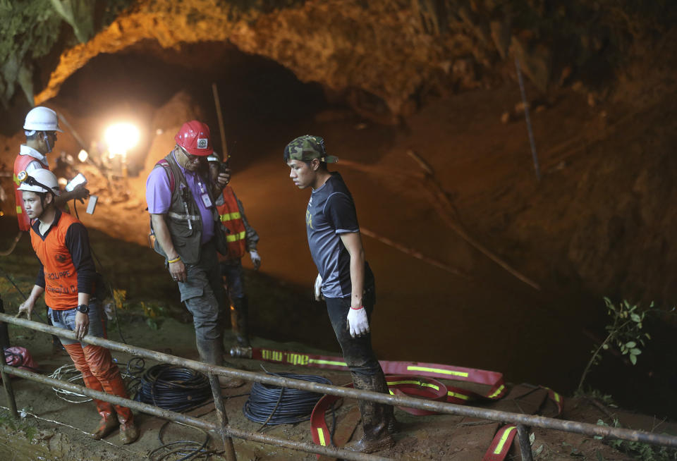 Rescue personnel walk out of the entrance of a cave complex. Source: AP