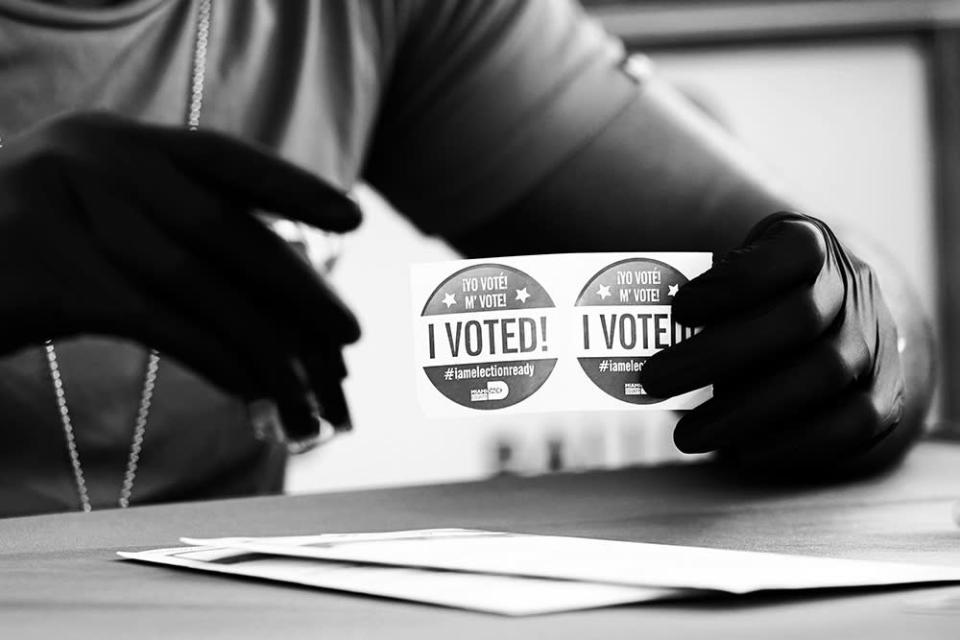 "An election worker holds ""I Voted"" stickers as people drop off their ballots for the Nov. 3 general election at the Miami-Dade County Elections Department in October 2020."
