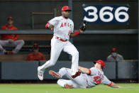 Los Angeles Angels left fielder Justin Upton (10) jumps to avoid right fielder Scott Schebler (44) as they both go to make the out on the fly by Houston Astros' Alex Bregman during the fourth inning of a baseball game Sunday, April 25, 2021, in Houston. (AP Photo/Michael Wyke)