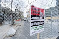 <p>A sign is placed on a fence around the makeshift 3rd police precinct on the day of closing arguments, April 19.</p>