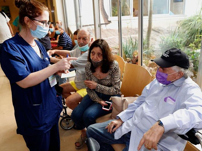 A woman in blue scrubs wearing a mask talks an older person wearing a black cap wearing a purple mask and white shirt while others wait sitting on chairs in the background.